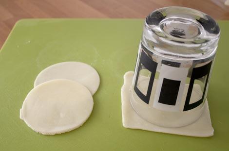 Cortar el queso mozzarella con forma redondeada con la ayuda de un vaso