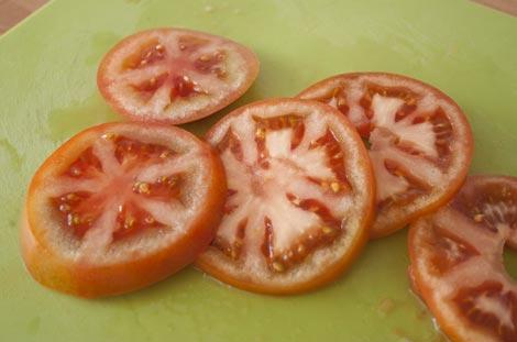 Cortar el tomate para hacer el milhojas con berenjenas y mozzarella