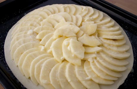Rociar la tarta de manzana con la mantequilla y el azúcar