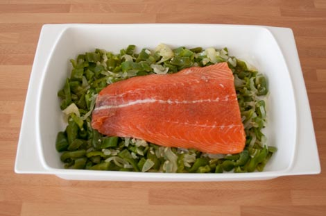 Colocar el salmón sobre la cama de verduras: pimiento verde y cebolla