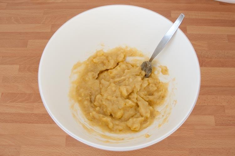 Machar los plátanos con un tenedor para hacer las galletas de plátano y avena veganas