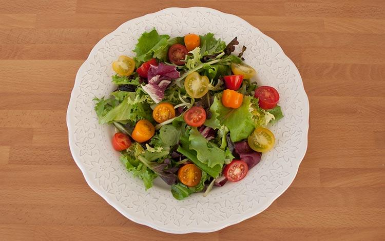 Colocar la lechuga, los tomates cherry y el resto de ingredientes de la ensalada de jamón de pato