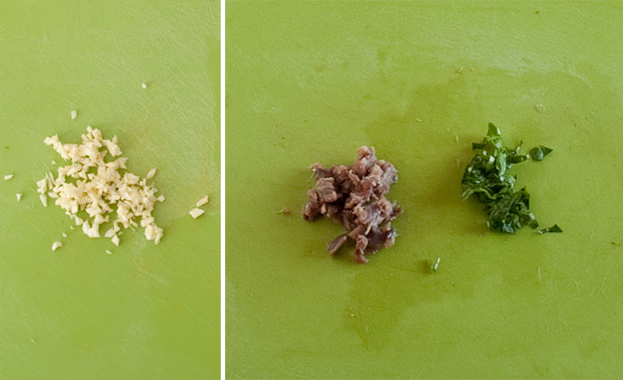 Picar el ajo, las anchoas y las hojas de albahaca