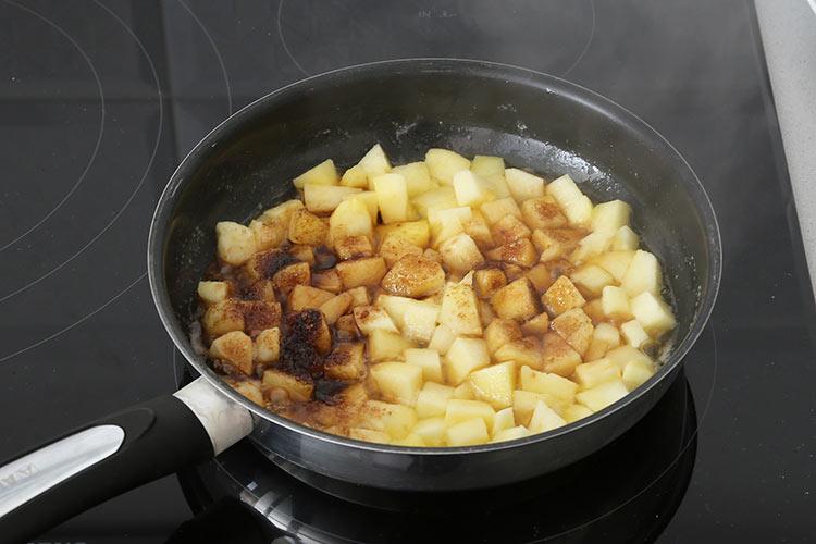 Cocinar la manzana con la mantequilla y el azúcar