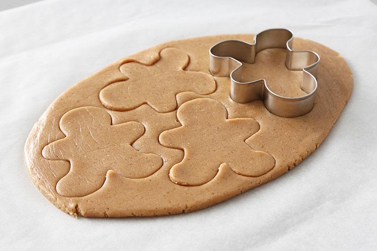 Cortar la masa de galletas con un cortador en forma de hombre de jengibre