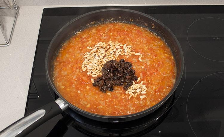Añadir los tomates, el vino, las pasas y los piñones. Cocinar hasta obtener una salsa