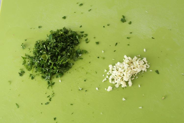 Picar finamente el ajo y el perejil para aliñar la merluz
