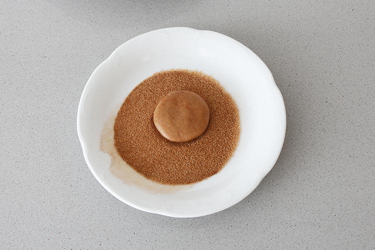 Aplastar las bolitas de galleta y rebozar una cara en azúcar y canela