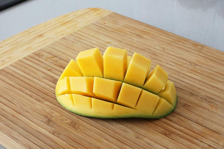 Dar la vuelta al trozo de mango y retirar los cubos