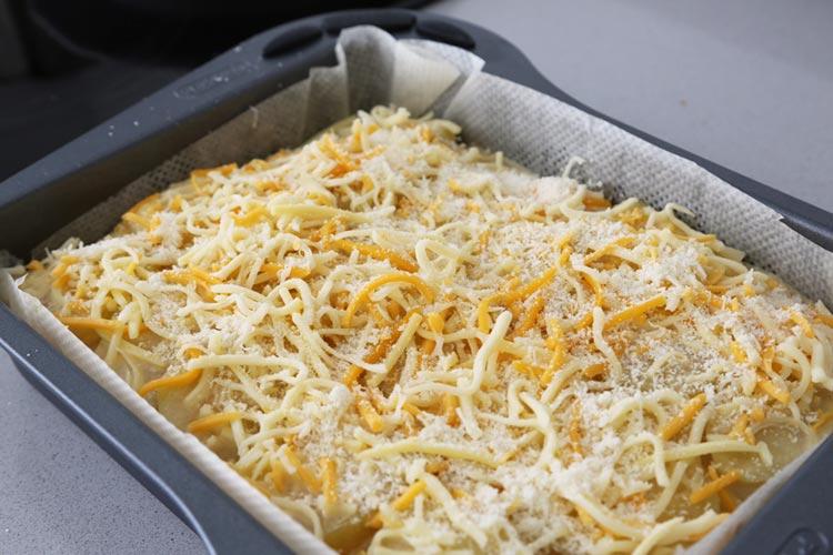 Cubre el pastel con el queso fundente y el parmesano