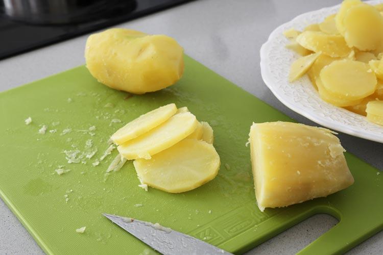 Cuece, pela y corta las patatas en rodajas