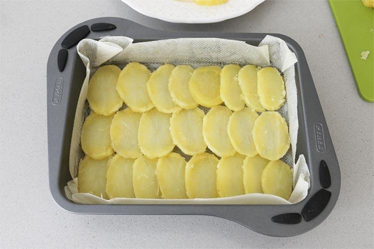 Cubre la base del molde con las patatas
