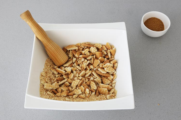 Tritura las galletas y mézclalas con la mantequilla y el azúcar