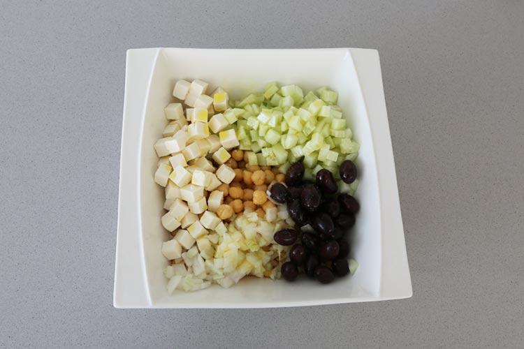 Mezclar los garbanzos con el pepino, el queso, la cebolla y las aceitunas negras