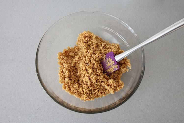 Triturar la galleta y mezclarla con el azúcar moreno y la mantequilla derretida