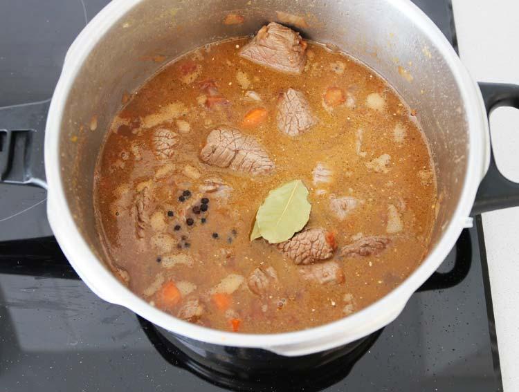 Incorporar la carne, la pimienta y el laurel al guiso