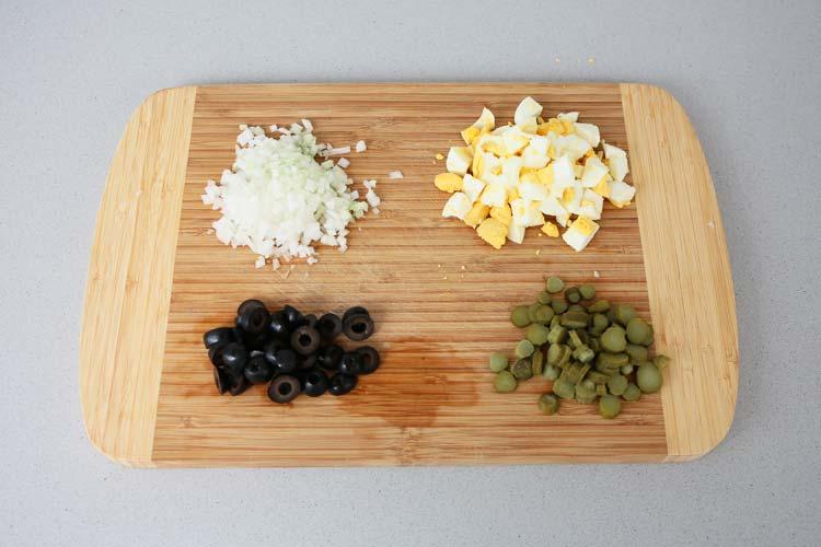 Picar la cebolla, los huevos duros, las aceitunas y los pepinillos en vinagre
