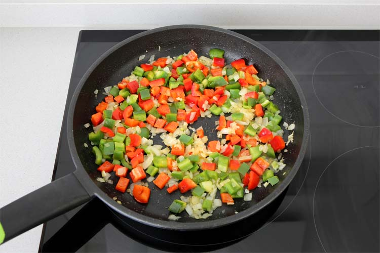 Pochar la cebolla, el ajo y los dos tipos de pimiento