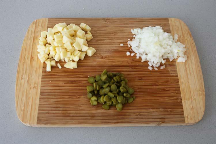 Cortar en cubitos la manzana, la cebolla y los pepinillos