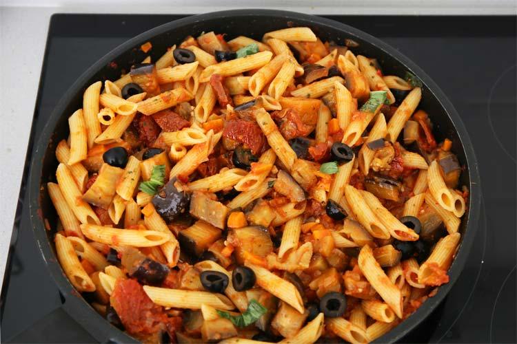 Incorporar la pasta cocida, las aceitunas negras, el tomate seco y la albahaca