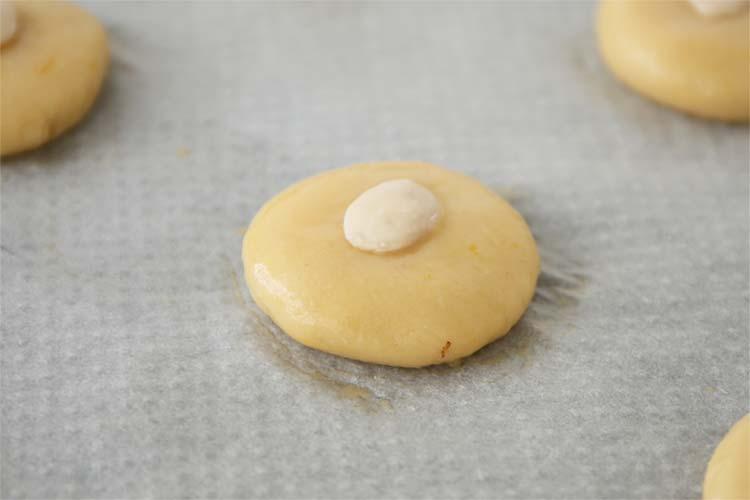 Dar forma a las pastas, pintar con huevo y decorar con una almendra
