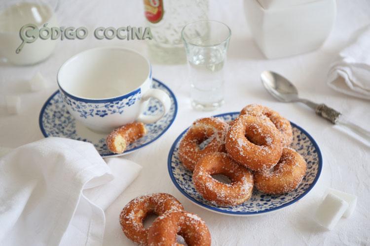 Rosquillas de anís caseras rebozadas con azúcar sobre un plato de postre.