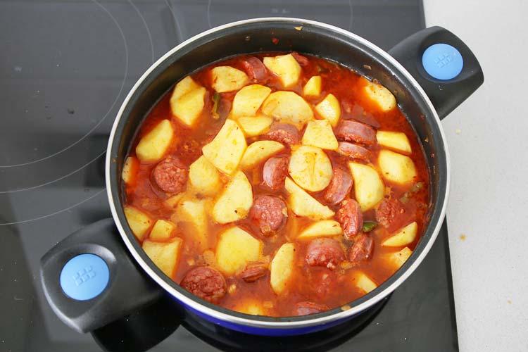 Añadir agua a las patatas con chorizo