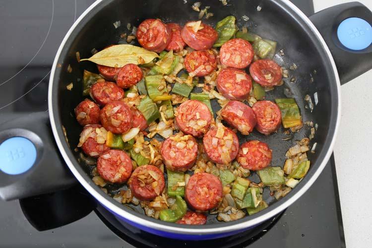 Sofrito de cebolla y pimiento verde con rodajas de chorizo fresco