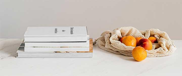 Bodegón con un diccionario de cocina y una bolsa con fruta