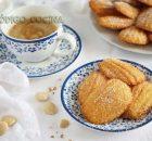 Madeleines de almendra fáciles colocadas sobre un plato con una tazá de café