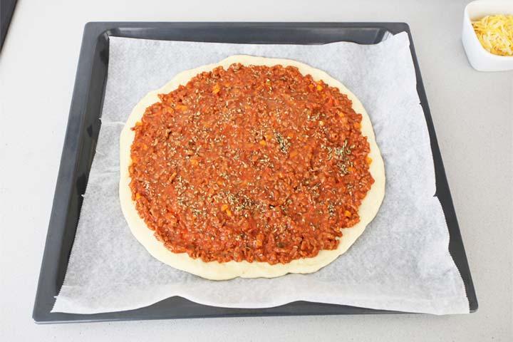 Colocar la salsa boloñesa sobre la masa de la pizza