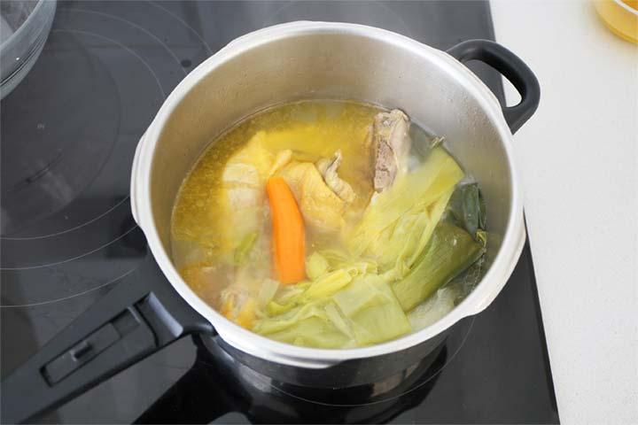 Olla con un caldo de pollo y verduras