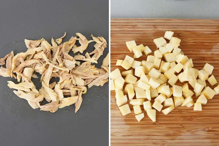 Pollo cocido y desmenuzado junto a una manzana cortada en dados