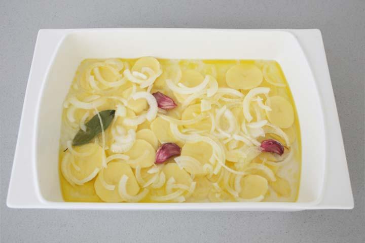 Rodajas de patata y cebolla en una fuente junto a unos dientes de ajo y una hoja de laurel