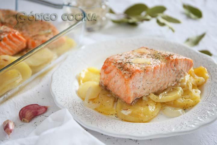 Salmón al horno sobre una cama de patatas y cebolla decorado con eneldo