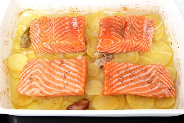 Trozos de salmón fresco colocados sobre una fuente de patatas